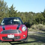 As red with black stripes Mini Cooper parked on a hill with trees and sky in the background and an accessibility tag hanging from the miror